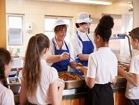 Image of school canteen staff serving pupils