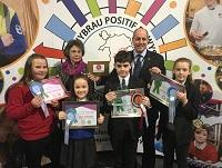 Image of judges and pupils with their poster competition prizes