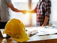 Image of yellow safety helmet on workplace desk with construction workers shaking hands