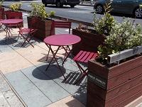 Image of table, chairs and planters on a pavement