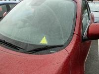Image of a car with a yellow triangle sticker in the window