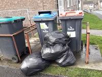 Image of fly-tipping outside flats in Ystradgynlais